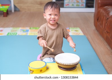 Cute happy smiling little Asian 2 - 3 years old toddler baby boy child hold sticks & plays a musical instrument drum in play room at home, Educational toy for kids and toddlers concept
