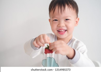 Cute happy smiling little Asian 2 -3 years old toddler baby boy child using hands eating strawberry, Healthy snacks & Self feeding concept