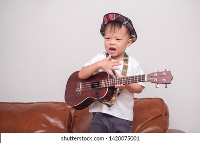 Cute happy smiling little Asian 2 - 3 years old toddler baby boy child wearing hat hold & play Hawaiian guitar or ukulele in living room at home, Music for kids and toddlers concept
