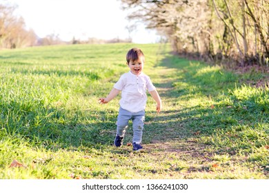 Cute happy smiling little baby boy in dirty jeans running on green grass among fields at bright sunny summer day. Childhood emotions