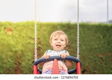 Cute happy smiling little child having fun riding on swing at children playground on sunny summer day with hig tounge out. Carefree childhood. Copy space. Close-up portrait