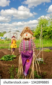 Cute happy straw filled boy scarecrow on allotments, made to guard the crops. A girl scarecrow is at the background.