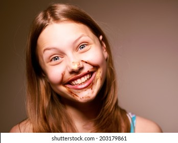 Cute happy teen girl having fun with chocolate on her face