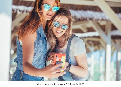Cute happy women in sunglasses make selfies on a smartphone while relaxing sitting in a straw booth while relaxing at the seaside. Concept of vacation in warm countries