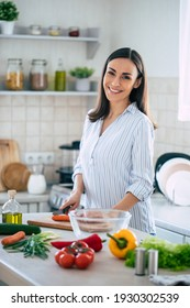 Cute happy young brunette woman in good mood preparing a fresh vegan salad for a healthy life in the kitchen of her home