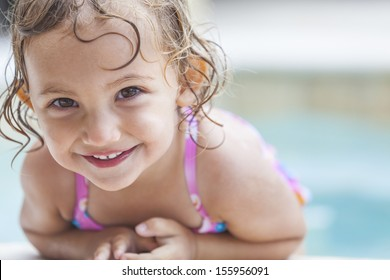 A cute happy young female girl child baby relaxing on the side of a swimming pool