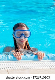 A cute happy young girl child relaxing on the side of a swimming pool wearing golubots goggles.