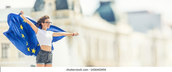 Cute happy young girl with the flag of the European Union in front of a historic building somewhere in europe.