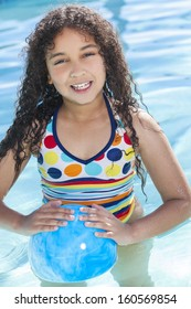 A cute happy young mixed race African American girl child playing in a swimming pool smiling with a blue ball