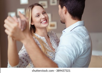 Cute happy young woman enjoying a dance in the arms of her husband as they celebrate a special occasion at home, close up head and shoulders view