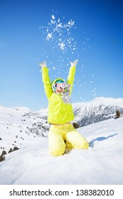 Cute happy young woman in green ski outfit throwing snow in the air