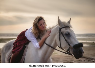 Cute happy young woman on horseback in summer beach by sea. Rider female drives her horse in nature on evening sunset light background. Concept of outdoor riding, sports and recreation. Copy space