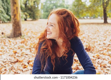 Cute happy young woman with tousled red hair relaxing in a park in autumn sitting amongst the fallen leaves looking to the side with a beaming smile