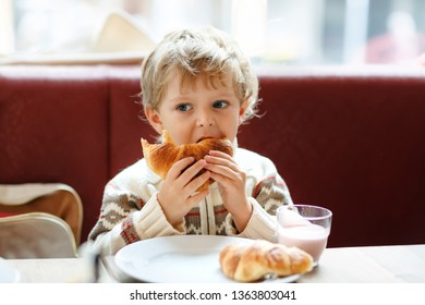 Cute healthy kid boy eating croissant and drinking strawberry milkshake in cafe. Happy child having breakfast with parents or at nursery. Vegetables, eggs as healthy food for children.