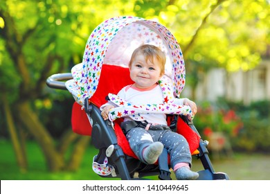 Cute healthy little beautiful baby girl sitting in the pram or stroller and waiting for mom. Happy smiling child with blue eyes. With green tree background. Baby daughter going for a walk with family
