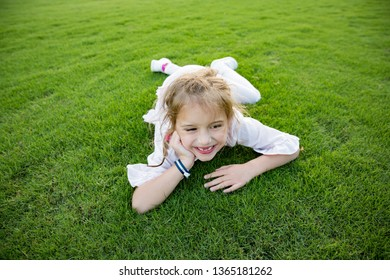 Cute healthy little girl lying on green lawn, smiling happily with toothless smile, screwing her eyes joyfully. Happiness and summer vacation