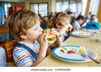 Cute healthy preschool boy eats hamburger sitting in school canteen