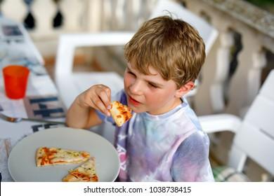 Cute healthy preschool kid boy eats fresh pizza sitting on terrace in summer, outdoors