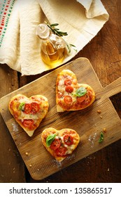 Cute heart shaped mini pizzas topped with cheese and tomato and garnished with fresh basil served on an old wooden board in the kitchen with virgin olive oil