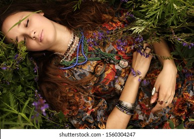 Cute hippie girl lies in a field in tall grass in a boho style clothing. Amulet.