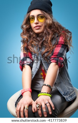 af4132e517c Cute hipster girl with long curly hair seating on chair wearing red  checkered shirt