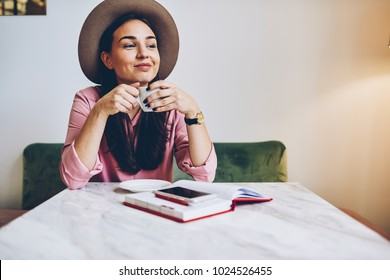 Cute hipster girl in trendy hat drinking coffee in morning enjoying starting day with favorite beverage,smiling attractive woman having work break in cafe interior thinking about plans for day