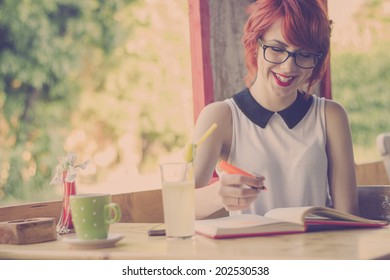 Cute hipster teenage girl reading a book and enjoying coffee