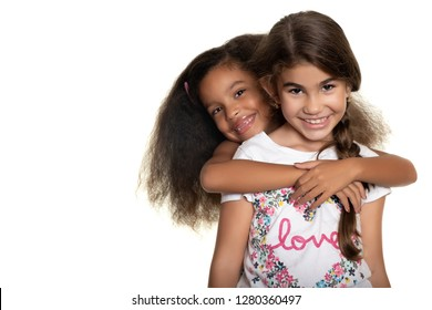 Cute hispanic and african-american small girls hugging with a smile - Isolated on white