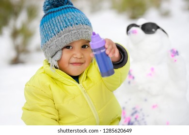 Cute Hispanic boy in winter clothes playing with paints and a snowman in a snow covered mountain during the winter season.