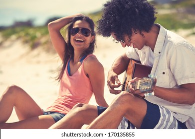 Cute hispanic couple playing guitar serenading on beach in love and embrace