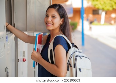 Cute Hispanic girl carrying some books and a backpack in high school