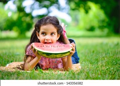 Cute hispanic girl eating watermelon at park