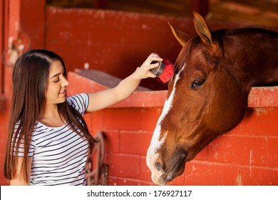 Cute Hispanic woman brushing a horse at the stables