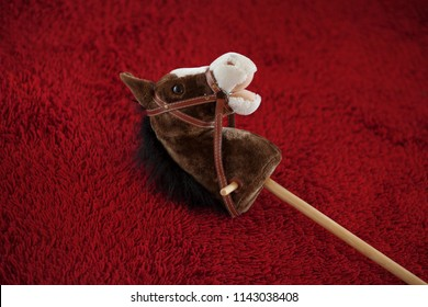 cute hobbyhorse lying on the floor on a red carpet, can be used as background