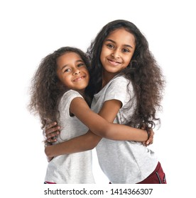 Cute hugging African-American girls on white background