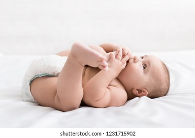 Cute hungry baby taking feet in mouth, lying on bed, copy space