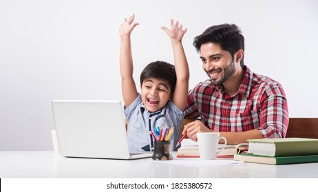 Cute Indian boy with father or male tutor doing homework at home using laptop and books - online schooling concept