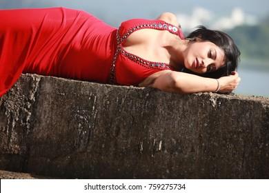 Cute Indian female model wearing red long dress posing outdoor in daylight