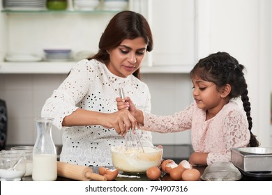 Cute Indian girl helping her beautiful middle-aged mother to beat eggs and flour with whisk while making dough for cupcakes, interior of small kitchen on background