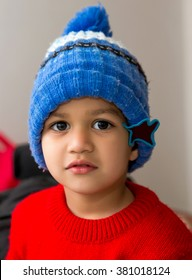 Cute Indian Kid striking a pose wearing red sweater and blue cap with a cute smile