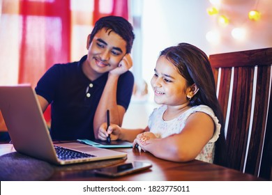 Cute Indian kids, boy and girl studying remotely on the laptop at home