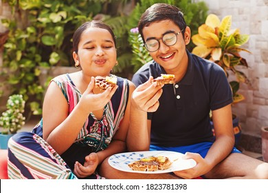 Cute indian kids, boy and girl eating delicious chocolate waffles outdoors at home