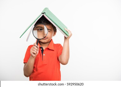 cute indian little boy holding book over head like roof, isolated over white background