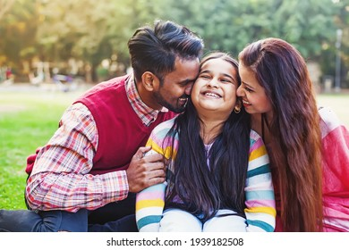 Cute Indian little girl being kissed by both of her parents on the cheeks outdoor in the park