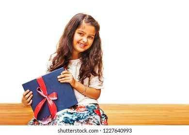 Cute Indian little girl holding a present