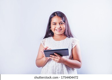 Cute Indian little girl using tablet computer on her studio portrait on white background