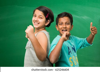 cute indian/asian school kids standing in front of empty green chalkboard background showing success or victory symbol with thumbs up