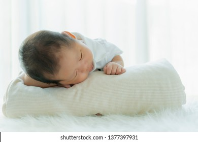 cute infant baby boy sleep with sweet dream and peaceful white soft bed