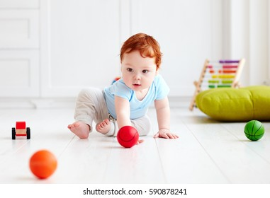 cute infant baby crawling on the floor at home, playing with colorful balls