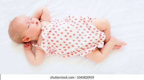 cute infant baby girl in bodysuit sleeping in bed. top view